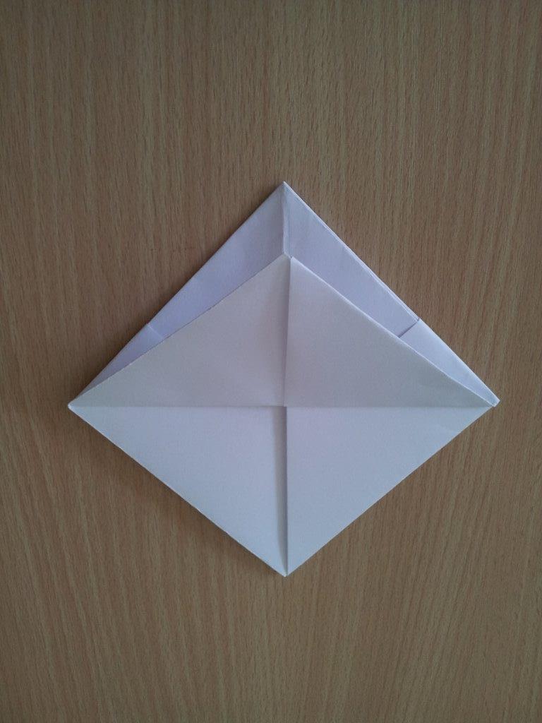 Faltet die lose Ecke des entstandenen Vierecks in der Mitte nach oben